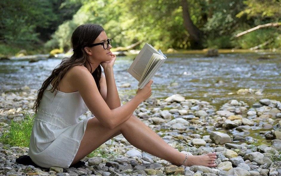 jeune femme au bord d'eau avec un livre